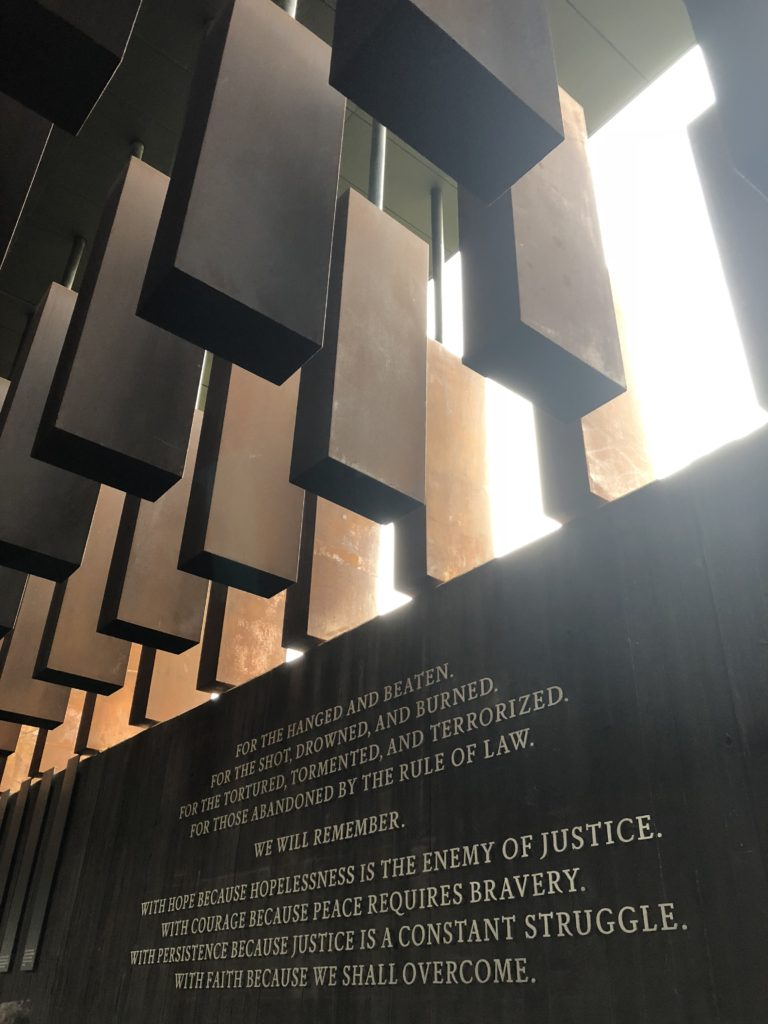 """Image from the National Legacy Museum - shows a wall with the quote """"For the hanged and beaten. For the shot, drowned, and burned. For the tortured, tormented, and terrorized. For the abandoned by the rule of law. We will remember. With hope because hopelessness is the enemy of justice. With courage because peace requires bravery. With persistence because justice is a constant struggle. With faith because we shall overcome."""""""